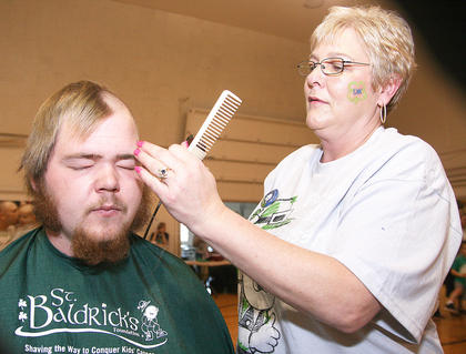 Jay Bland sits as Connie Smith prepares to shave his hair and his muttonchops.