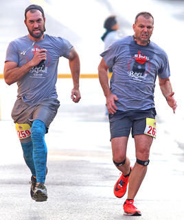 Derrick Mack (left) and Barry Shewmaker (right) race to cross the finish line at the All Fired Up About Baseball 5K in March. Shewmaker beat Mack by two seconds.