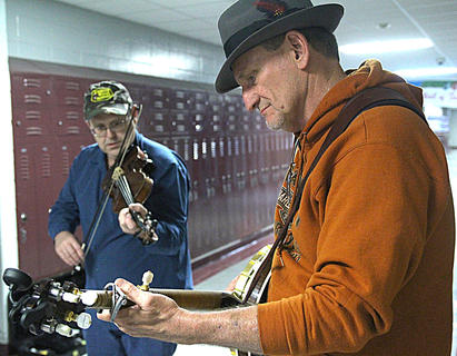 Alan Lewis of Danville plays the banjo, and Doug Jarvis of Mercer County plays the fiddle during a short jam session Saturday afternoon in a hallway at Marion County High School.