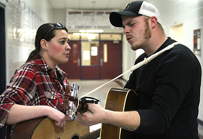 "Ashley Knapp and Cody Doench, both of Dayton, Ohio, play a song Saturday afternoon in the halls of Marion County High School. Knapp won this year's singer-songwriter contest with her song, ""Justified."""