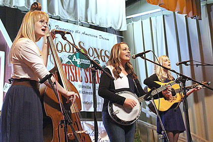 From left, Amelia John, Chloe Blayne and Andrea Brooke of the Blue Belles take the stage at the Kentucky Bluegrass Music Kickoff on Friday evening.