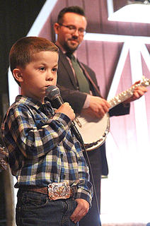 """Joshua Raikes sings Friday evening with Paul Harrigill playing banjo in the background. This performance took place during """"Come Play With Biscuit"""" Friday evening of the 2016 Kentucky Bluegrass Music Kickoff."""