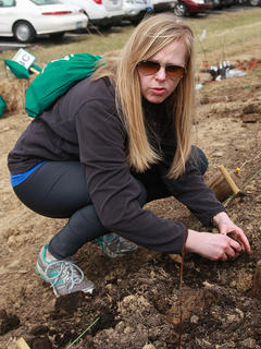 Madeline O'Nan plants trees as part of team representing the New Pioneers for a Sustainable Future.