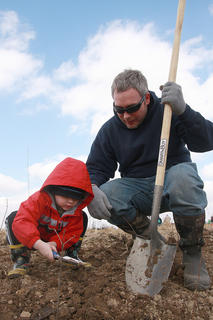 Jay Thomas offers some instructions as his son, Nolan, 4, packs soil around a newly planted seedling.