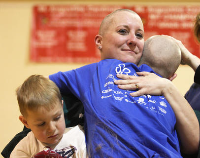 Teresa Albright gets a hug from her daughter, Emma, while getting her head shaved at St. Baldrick's. She is holding her son, Eli. Albright is part of the team Casper and the Looneytunes, who shaved their heads in honor of Albright's mother, Sue Beavers, who is undergoing treatments for non-small cell lung cancer.
