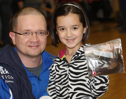 Amira Bowman, pictured with her father, Jeremy, brought a donation of her own hair for Locks of Love, which uses donated hair to make wigs for chemotherapy patients. Bowman shaved his in support of his daughter's donation to Locks of Love.