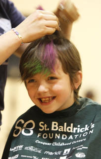 Eli Potters is all smiles while waiting to have his/her head shaved at St. Baldrick's.