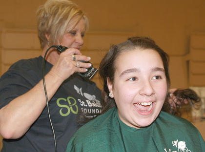 Alex O'Bryan, 13, of Bardstown seems a little surprise after stylist Carol Curtsinger takes off the first piece of her hair. O'Bryan shaved her head in honor of her brother, Joe Charles, 7, who is undergoing treatment for brain cancer.