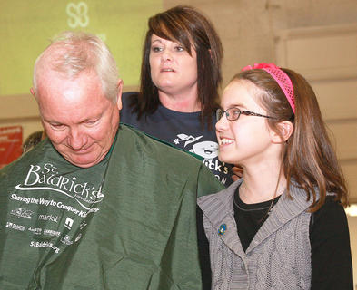 Bob Abell sits for a head shave as his granddaughter, Avery Leachman, 9, of Louisville watches. Avery is this year's St. Baldrick's ambassador child. Last year, she was diagnosed with papillary thyroid cancer. Abell's stylist is Candi Skaggs.