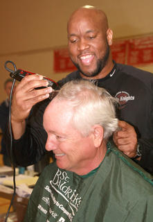 Honorary barber Anthony Epps starts the shaving by shearing Bob Abell of team Bobarazzis during the 2013 St. Baldrick's, which was held March 23 at St. Augustine School. Abell is the grandfather of Avery Leachman, this year's ambassador child.