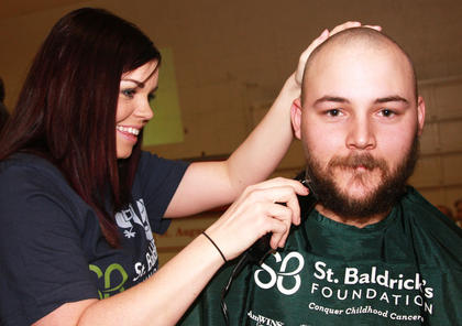 Stylist Robyn Wood goes to work on Adam Moore's beard. Moor is a member of the team Casper and the Looneytunes.