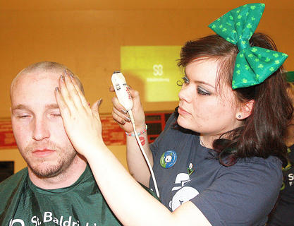 Taylor Claypool brushed hair away from the eyes of Jason Beard of Loretto. This is Beard's first year participating in St. Baldrick's.