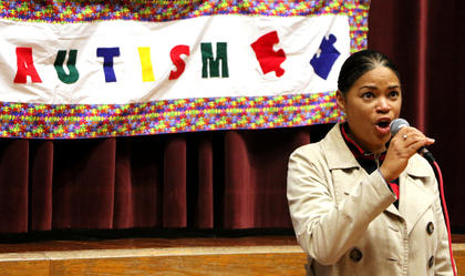 Angela Crenshaw sings the National Anthem at the Working the Puzzle for Autism event Saturday morning.