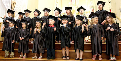 Three-year-old and four-year-old preschoolers perform a special song during the graduation ceremony.