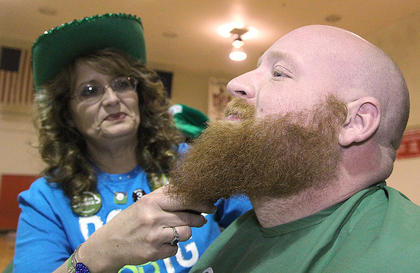 Brett Childers offers up his beard for the fourth time at St. Baldrick's. Kim Childers does the honors.