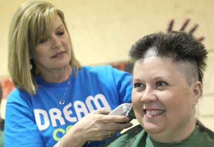 Trava Vaught sits to have her head shaved by Eileen Hughes. Vaught's granddaughter, Ellie Hurley, 3, is undergoing treatment for acute lymphoblastic leukemia.