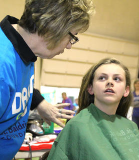 Lilly Clark, 11, chats with stylist Darlene Morgan about how short she wants her hair cut. Clark told her to shave it all the way.