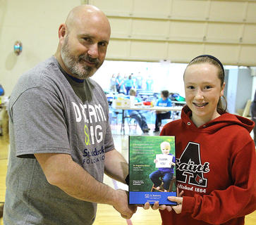 Shawn Gibson of Citizens National Bank presents a token of appreciation to St. Augustine School for being the host site for St. Baldrick's for the past nine years. Eighth-grader Brook Smith accepted on behalf of the school.