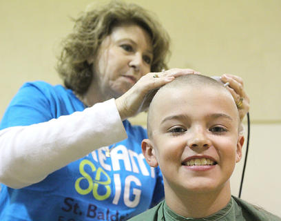 Stylist Polly Miller shaves the final bit of hair from J.T. Mattingly's head.