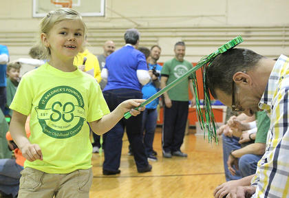 Kaylee Clark, 6, knights the newest members of the Knights of the Bald Table, individuals who have participated in St. Baldrick's for seven years.