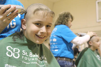 Gavin Bartley, 10, smiles just before the final tufts of hair are removed from his head.