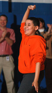 Sixth-grader Nathan Hunt waves to the audience after a slideshow of fashion designs he created.