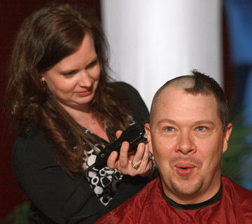 Jennifer Russell, LMS media specialist, does the honors by shaving Bobby VanDyke's head.
