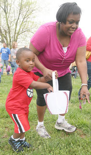 Jamaruie Walker, 2, of Lebanon gathers eggs as his aunt, Christina Furmon, offers some guidance.