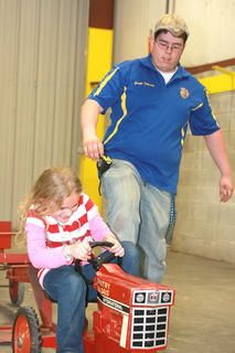 Makayla May. 10, gets a little help from Joseph Peterson getting started in the pedal pull Saturday afternoon.