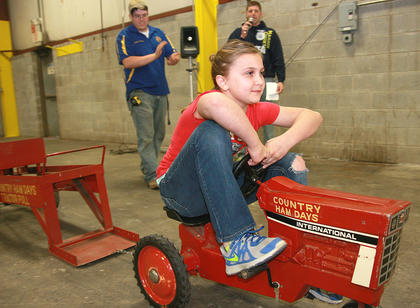 Kaylee Buckman, 10, gets off to a smooth start in the pedal pull as Joseph Peterson, left, and Daniel Mattingly cheer for her.
