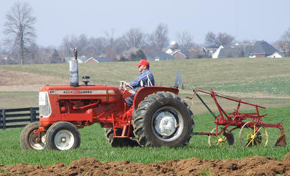 Jody Hughes pulls one of his brother's antique plows behind an oranges Allis Chalmers tractor.