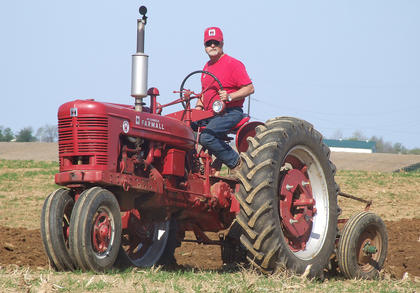Mike Craig wears a hat and shirt to match his Farmall Super H.