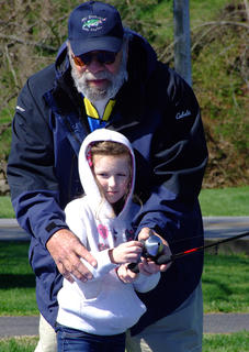 Shelton Young helps Isabella Turner, 6, of Lebanon with her casting and fishing technique.