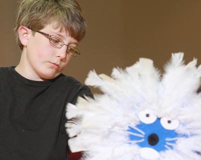 Fourth grader Eli Nelson performs with a mash covered with feathers.