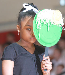 Fourth grader LaTasia Johnson hides behind her mask as the dance routine begins.