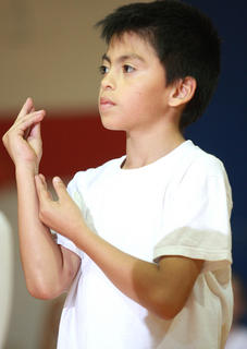 "Second grader Junior Garcia performs a series of hand gestures choreographed with ""Hero"" by Mariah Carey."