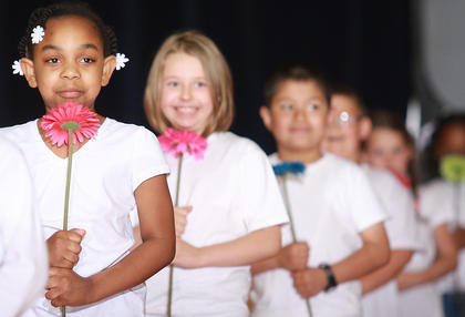 """Lexus Moffitt, Kaylee Leake and Noe Serrano hold flowers at the start of the first graders' routine to """"Count on Me"""" by Bruno Mars."""