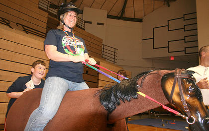 Andrew Geyer, 10, of Lebanon helps rock the horse as his mother, Diane Driscoll, gives it a try.