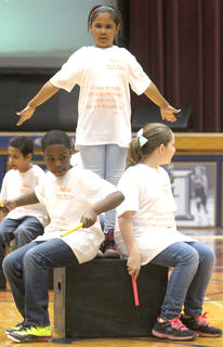 Third-grader DeShaila Newby dances atop a platform, as Taylon Johnson and Sidney Click use the platform as a percussion instrument.