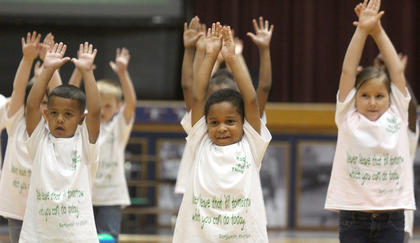 "From left, kindergartners Xavier Hayden, Pejaun Owens and  Nora Rigdon reach during a routine to ""The Distance"" by Cake."