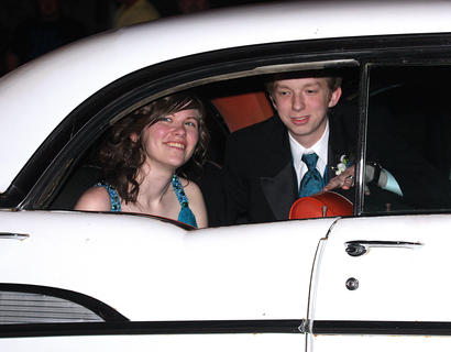 Katie Wyman gives a playful smirk to the crowd as she and Blake Tharp prepare to get out of their stylish ride and walk into prom.