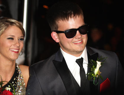 Clay Rogers smiles at the crowd as he and his date enter prom.