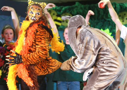 Baloo (Jared Tutt) grabs the tiger Shere Khan (Abbe George) by the tail as part of the effort to save Mowgli.