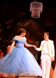 Cinderella, played by Emma Humphress, and Prince Charming, played by Zachary Brady, join hands for their first dance at the royal ball.
