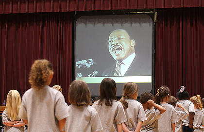 Students prepare to perform as they listen to the words of Dr. Martin Luther King Jr.