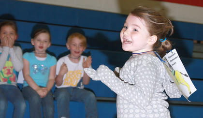 Kindergartner Arora Norris can't hide her smile as she crosses the finish line in first place.  Avery Newton, Brayden Brown and Thomas Carrico watch from the bleachers.