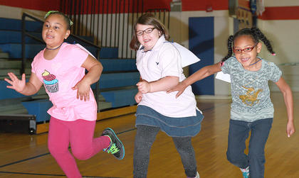 Kindergartners Aleea Sickles, Dezaray Settles and Xiamiah Scott scramble for position to start the race.