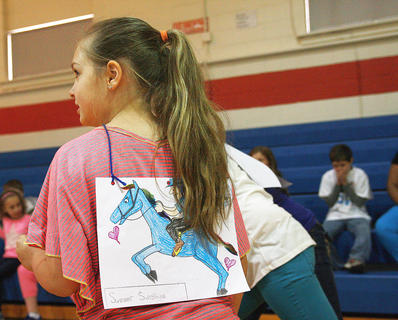 """Fourth-grader Summer Votaw, a.k.a. """"Summer Sunshine"""", lines up at the starting line. Each student decorated and named a picture of a horse for the races."""