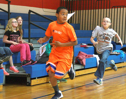 Fourth-grader Omarrion Burch looks back to see how close Adam Hardin is. On the bleachers, Loryn Hardin and Bailey Hernandez watch the action.