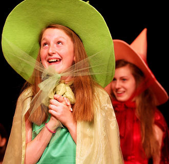 Sydney Raikes plays the part of Fauna. Pictured in the background is Gaubrielle Humphress.